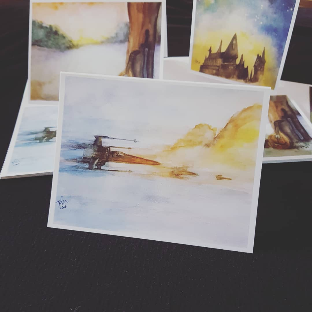 notecards with watercolour prints of hogwarts, xwings in flight, and kvothe's lute and sword